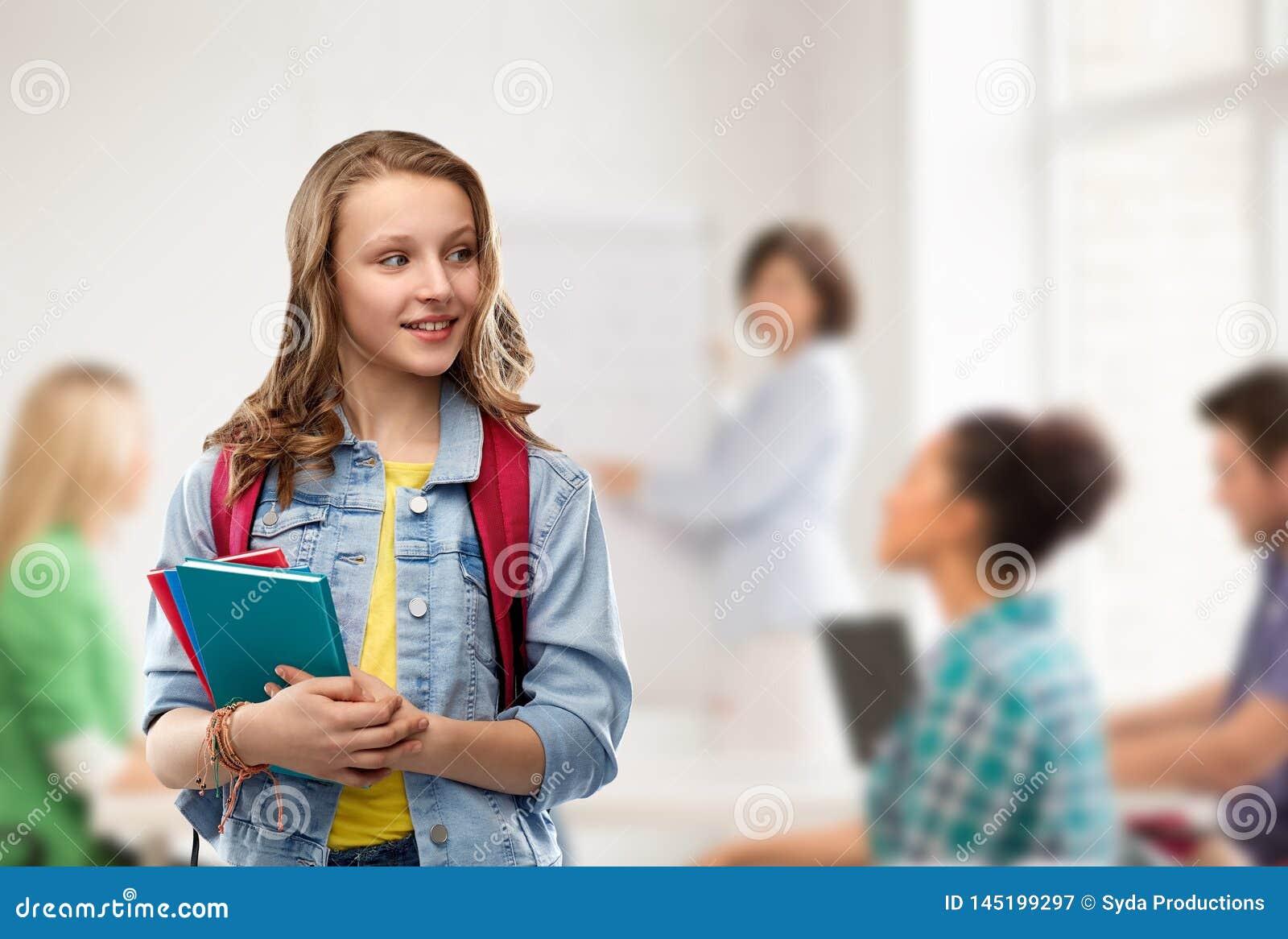 Lycklig le ton?rs- studentflicka med skolap?sen