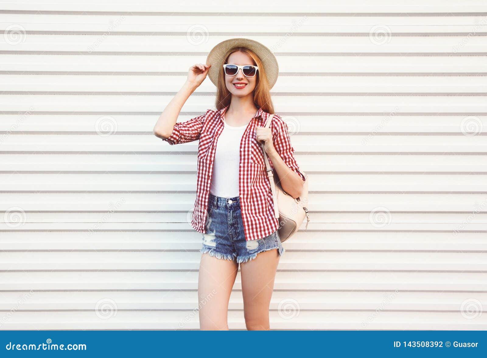 Lycklig le ung kvinna i hatten för sommarrundasugrör, rutig skjorta, kortslutningar som poserar på den vita väggen