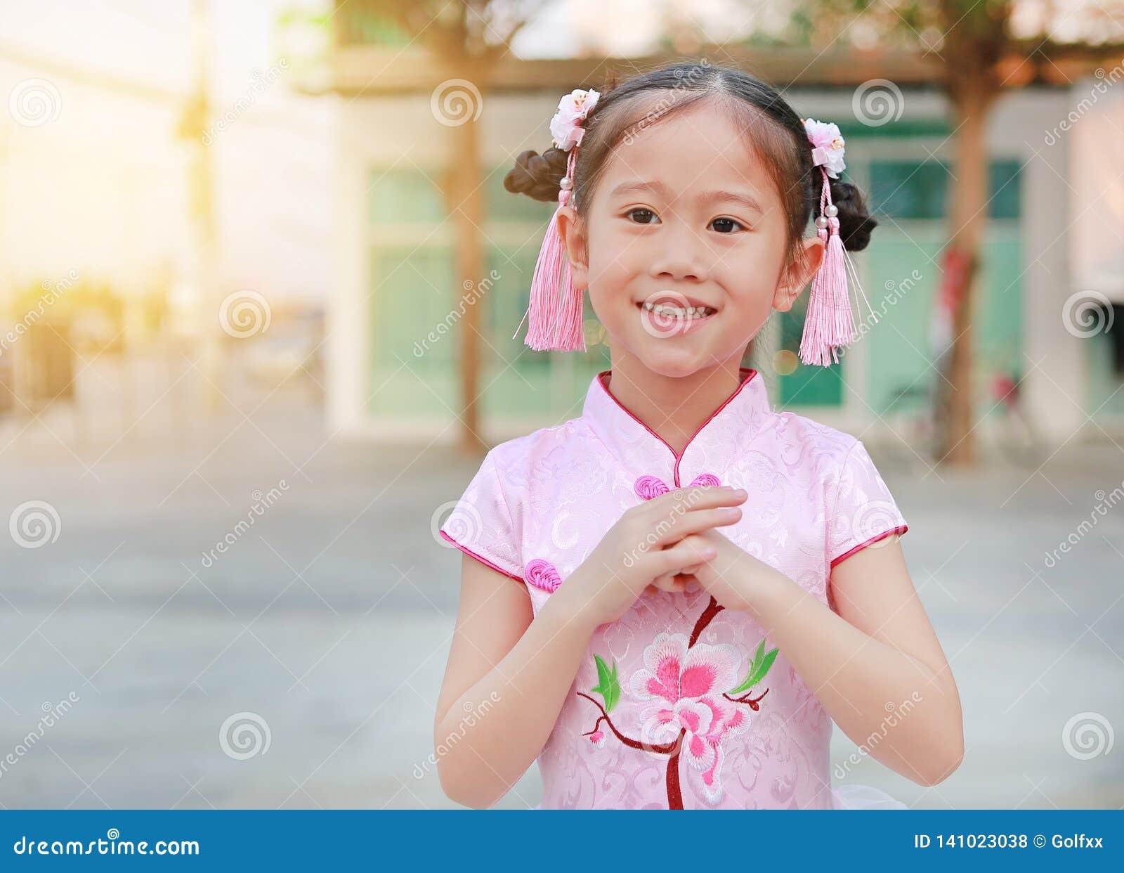 Lycklig liten asiatisk barnflicka som bär den rosa traditionella kinesiska klänningen med hälsninggestberöm för kinesiskt nytt år