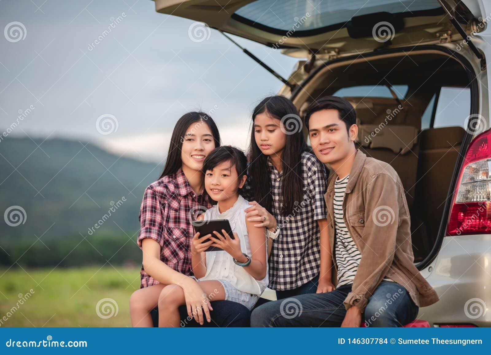 Lycklig liten flicka med asiatiskt familjsammantr?de i bilen f?r att tycka om v?gtur och sommarsemester i camparesk?pbil