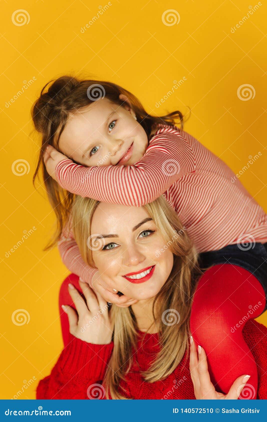 Lycklig liten flicka med hennes unga moder på den gula bakgrunden Dotter som sitter på mammas hals leende