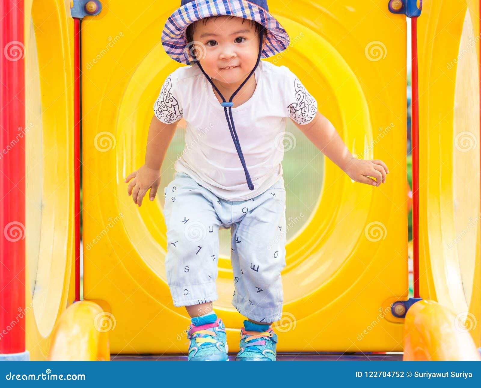Lycklig liten flicka som spelar på lekplatsen Barn som är lyckliga, fa