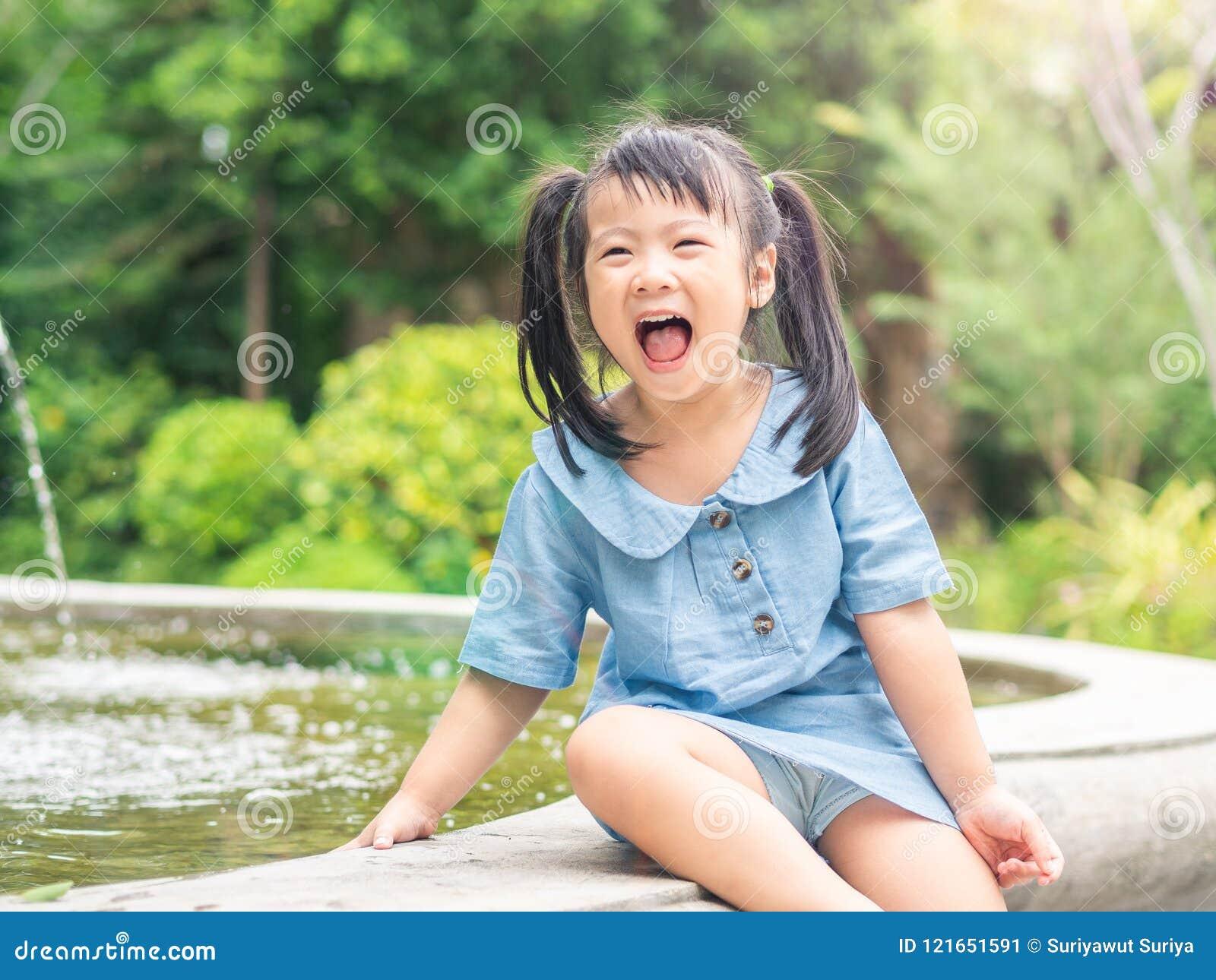 Lycklig liten flicka som spelar på springbrunnen på bokehbakgrund H