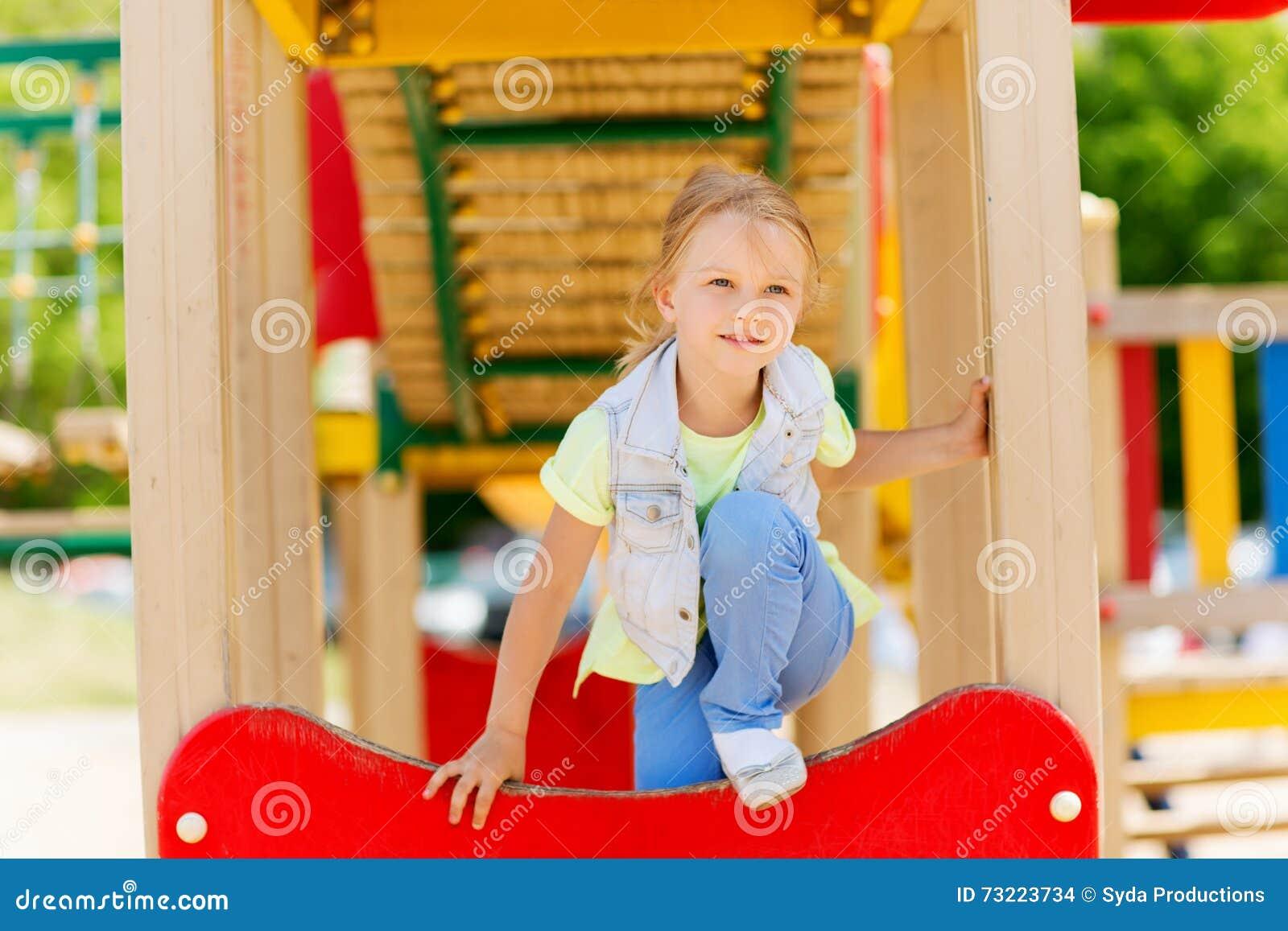 Lycklig liten flickaklättring på barnlekplats