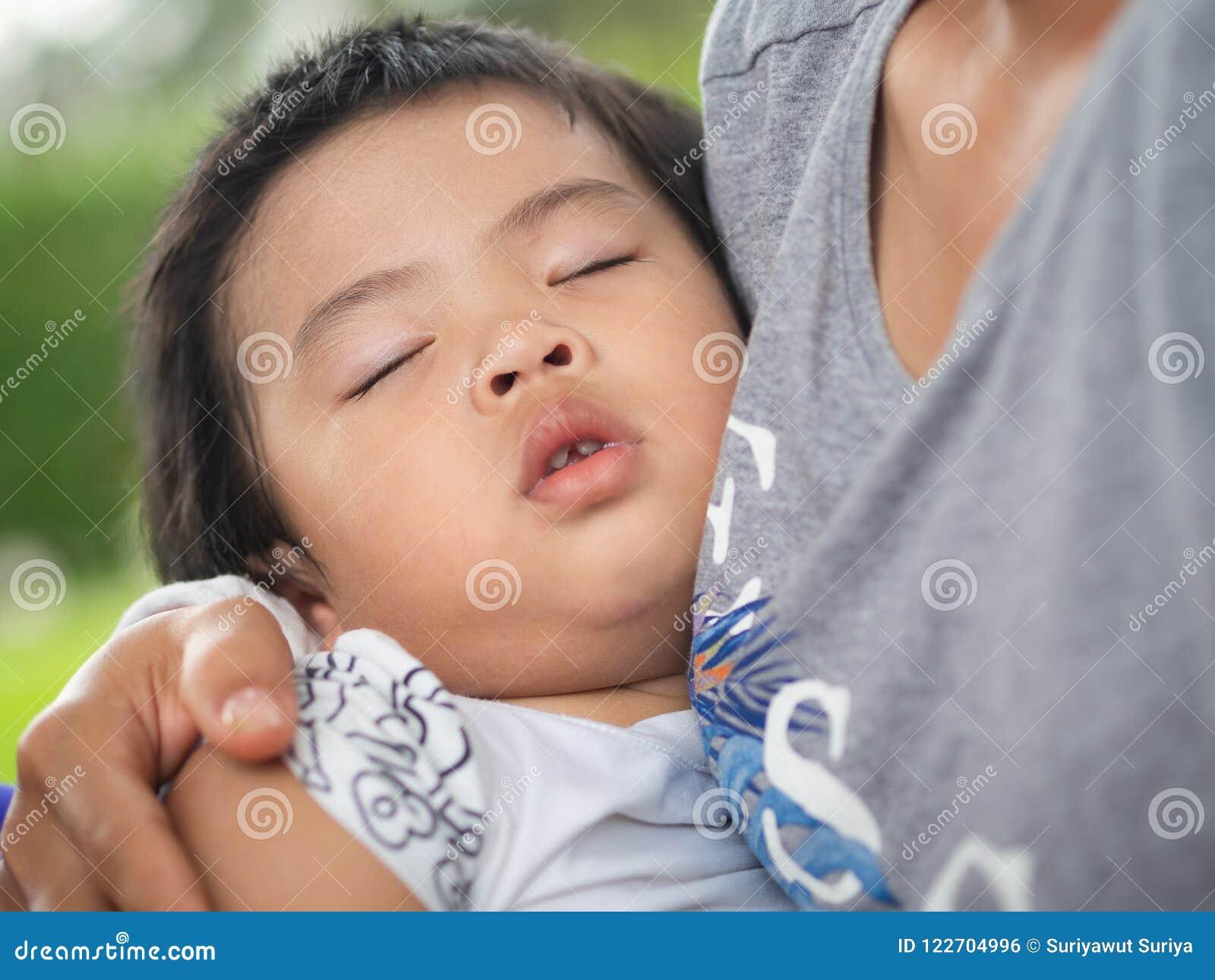 Lycklig liten gullig flicka som sover i kram för moder` s i parkera Familj förälskelse, lyckligt begrepp