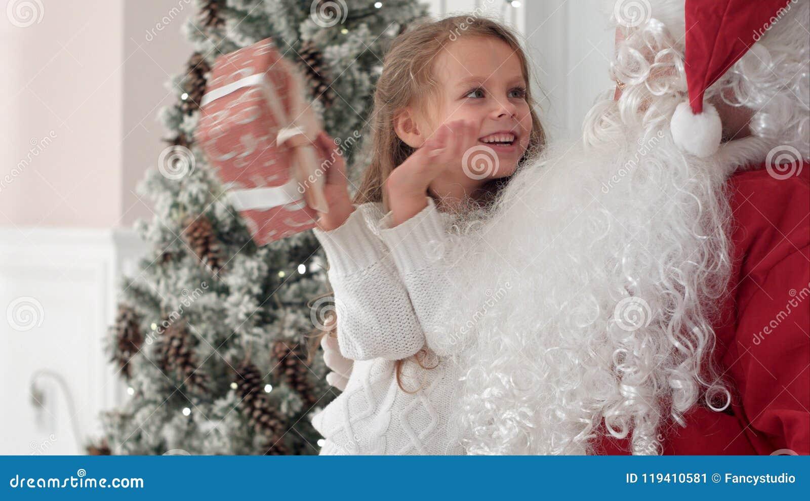 Lycklig liten le flicka som försöker att gissa vad är inom hennes julgåva från jultomten