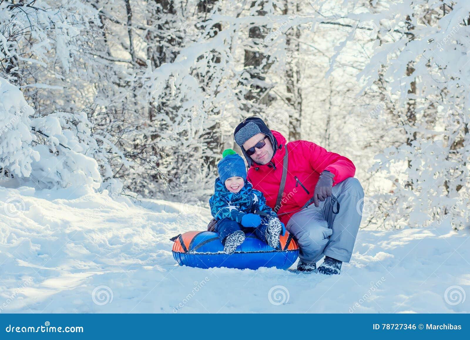Lycklig litet barnpojke med farsan i den snöig skogen