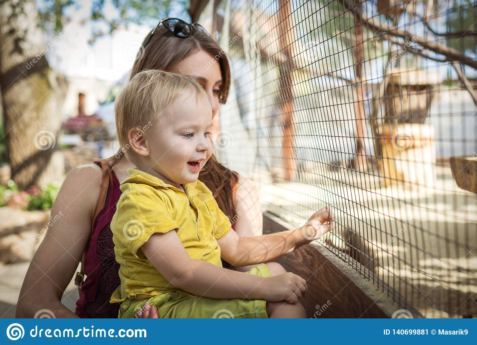Lycklig litet barnpojke och hans ung moder som ser djuret på zoo