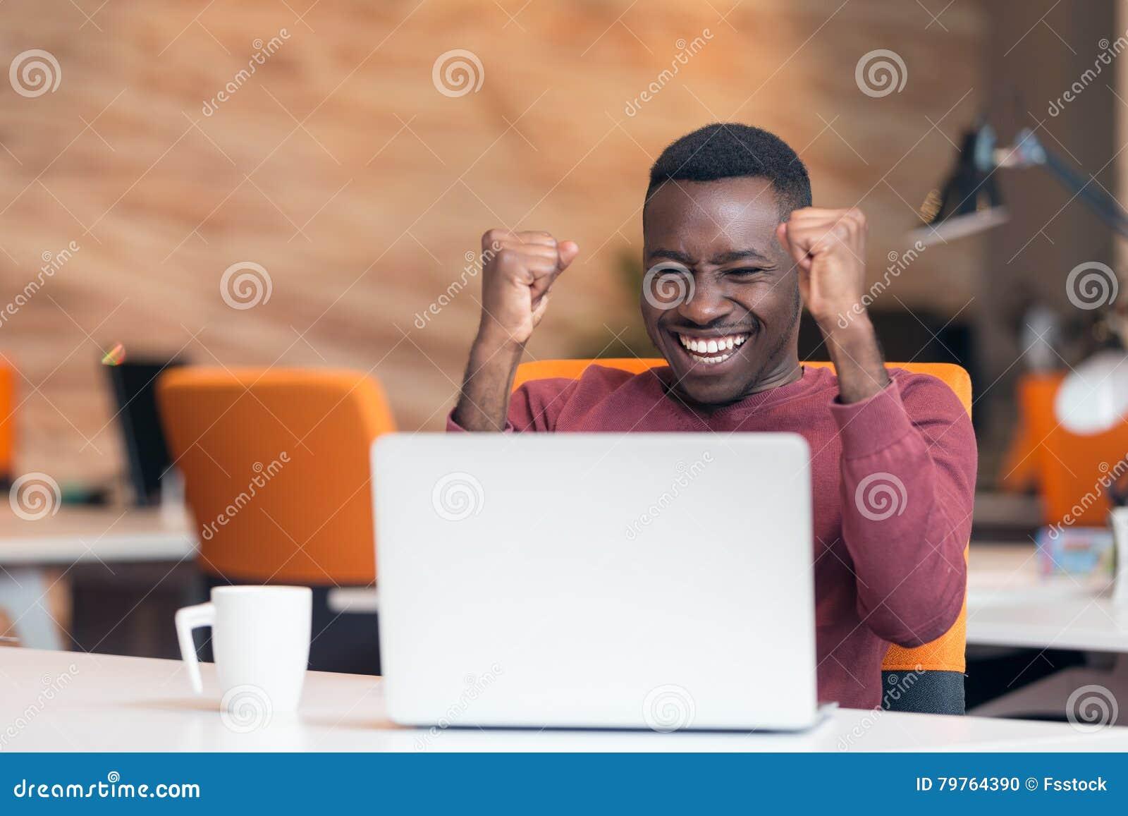 Lycklig lyckad afrikansk amerikanaffärsman i ett modernt startup kontor inomhus