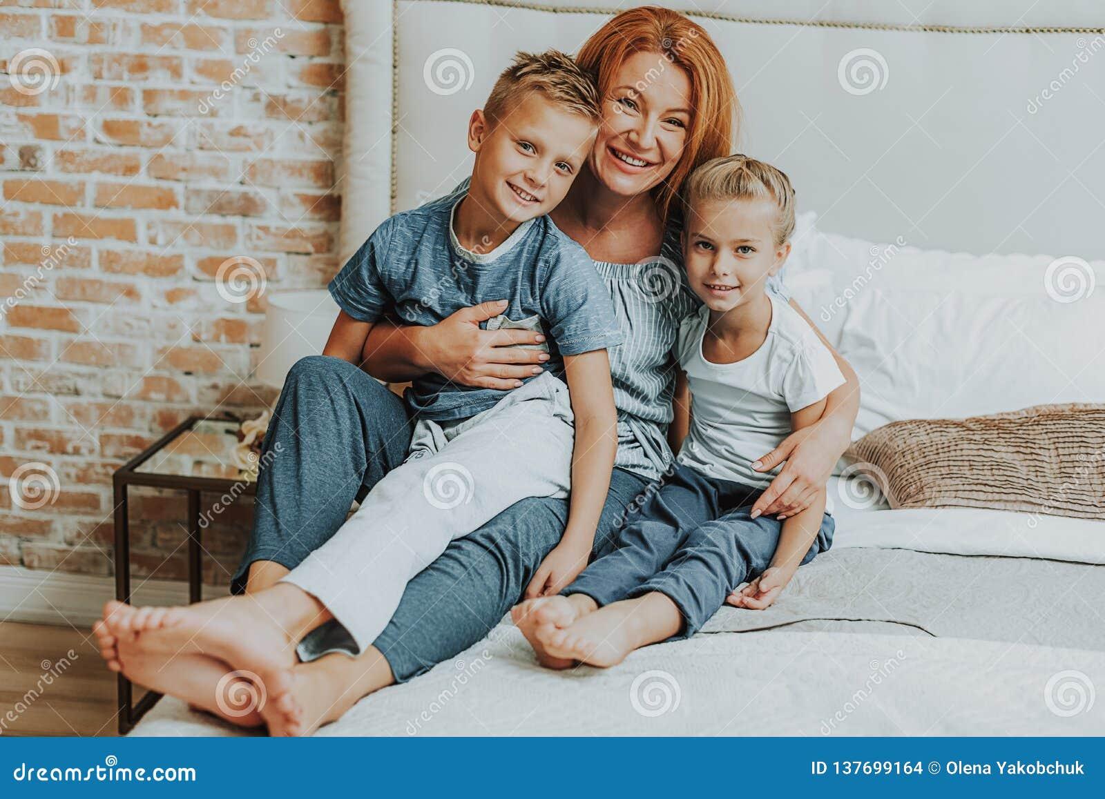 Lycklig mamma och två ungar som kopplar av i säng