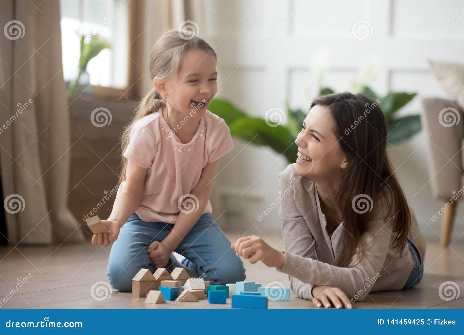 Lycklig mamma- och ungedotter som skrattar att spela med träkvarter