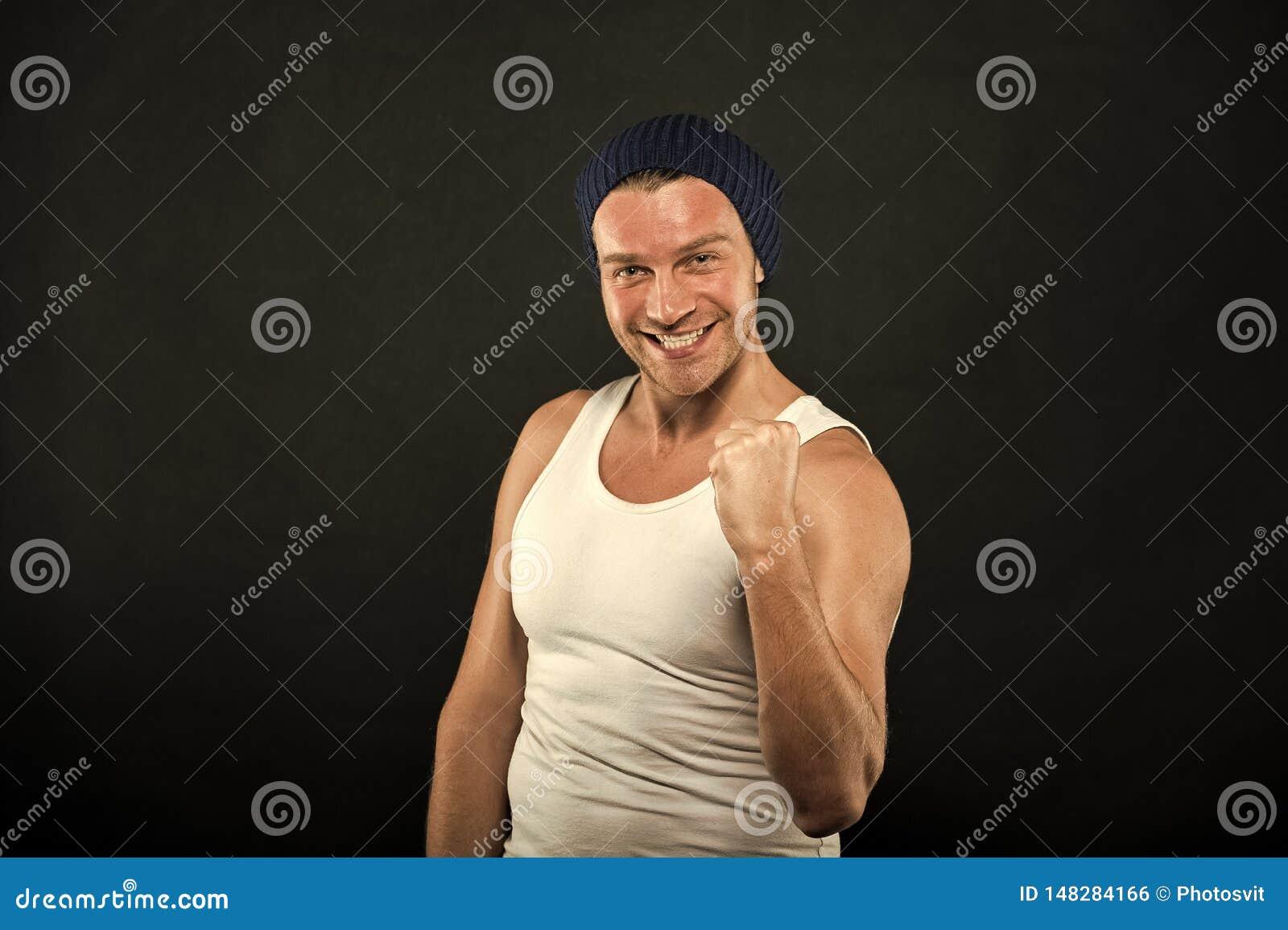 Lycklig man med vinnaregest Macho leende i tillf?llig v?st och hatt p? m?rk bakgrund Idrottsman med borstet p? att le