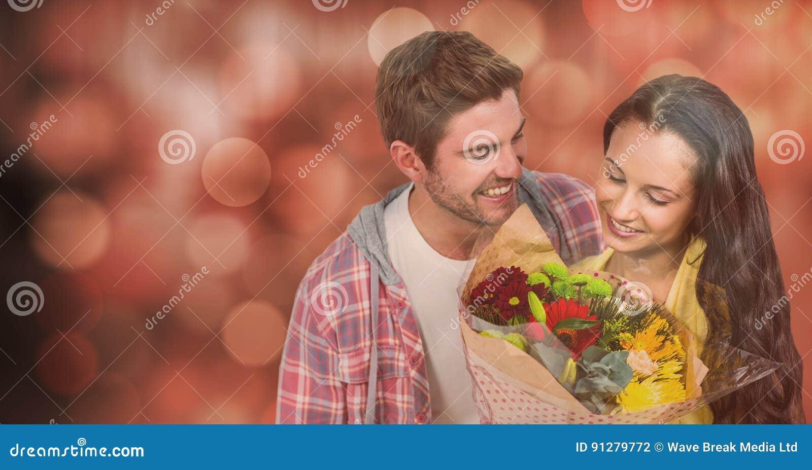 Lycklig man som ser kvinnan med blommor över bokeh