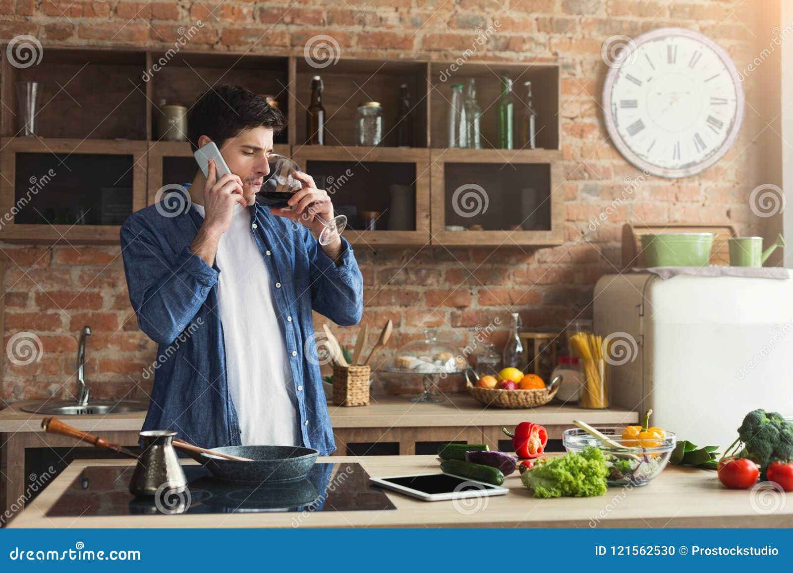 Lycklig man som talar på telefonen och dricker vin i kök