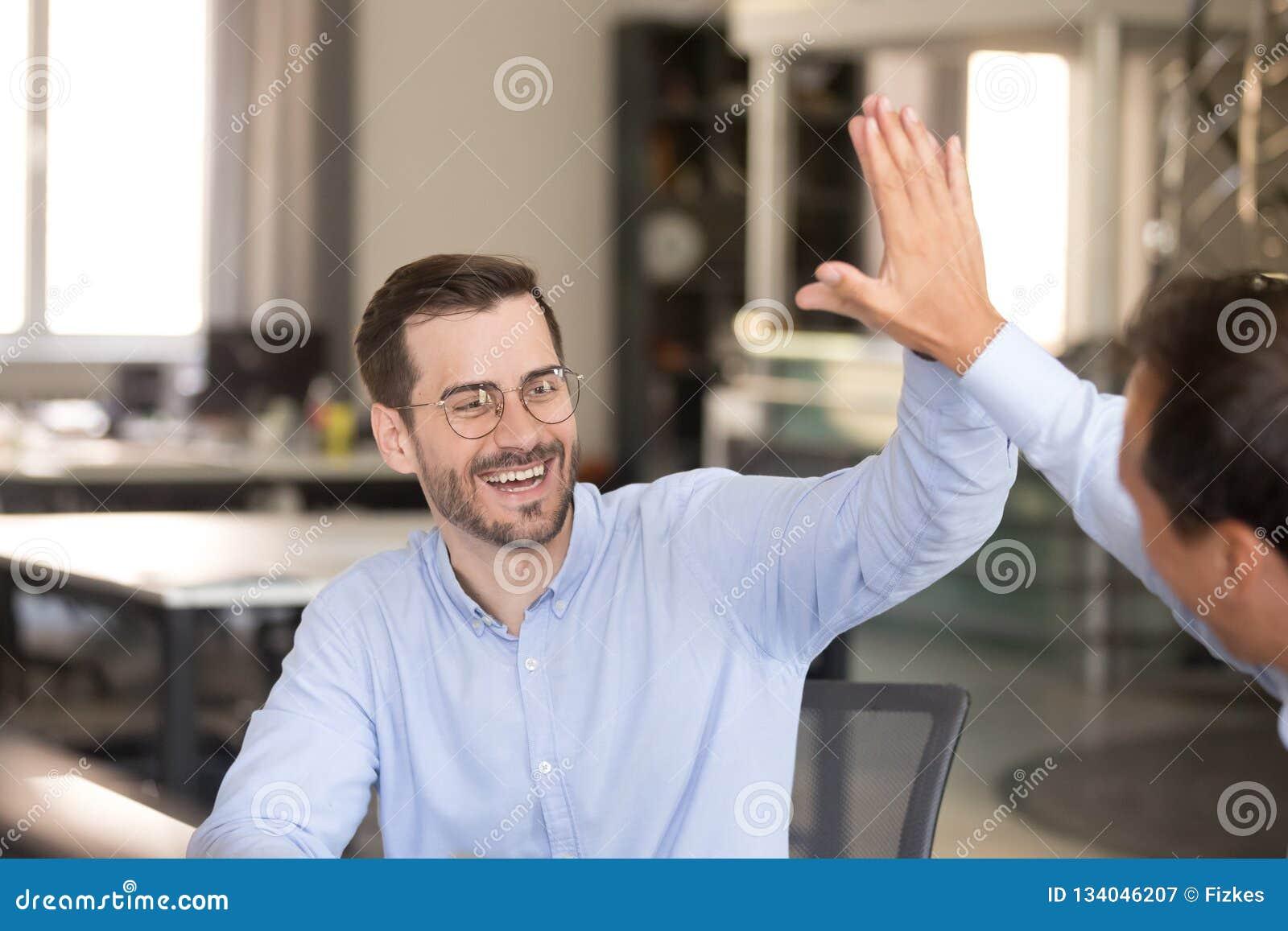 Lycklig manlig anställd som ger högt fem till kollegan