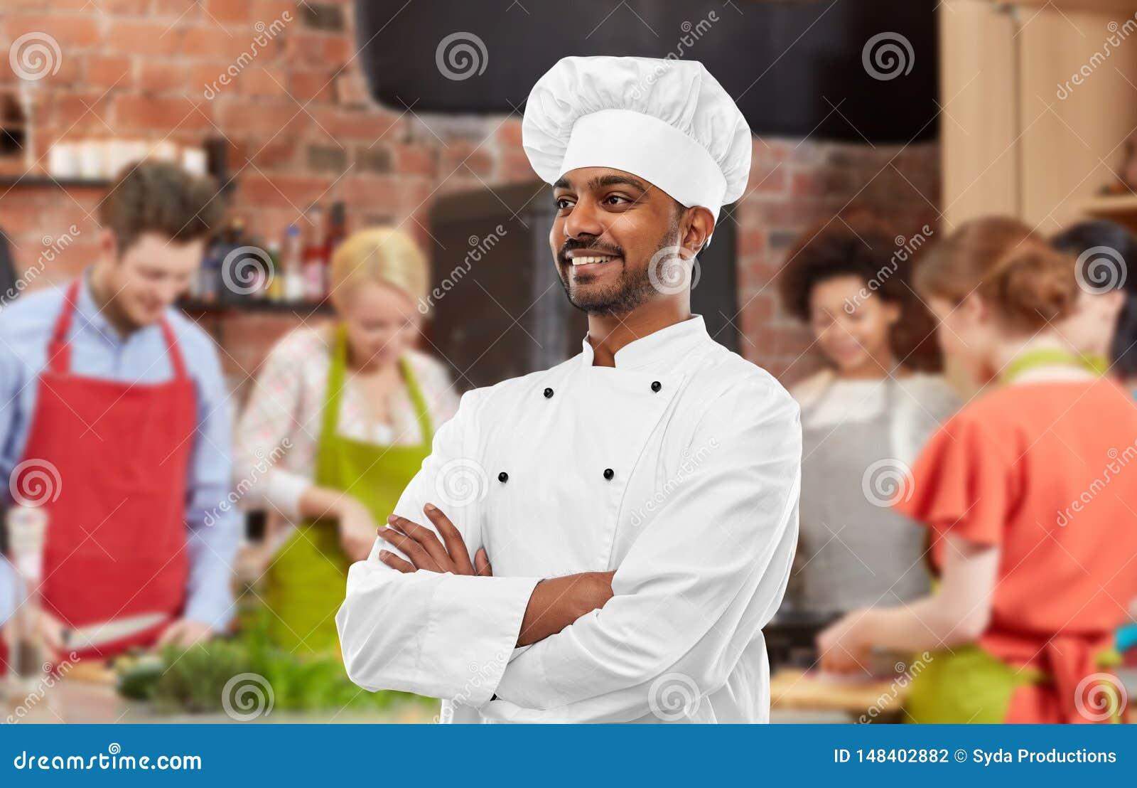 Lycklig manlig indisk kock i toque p? matlagninggrupp