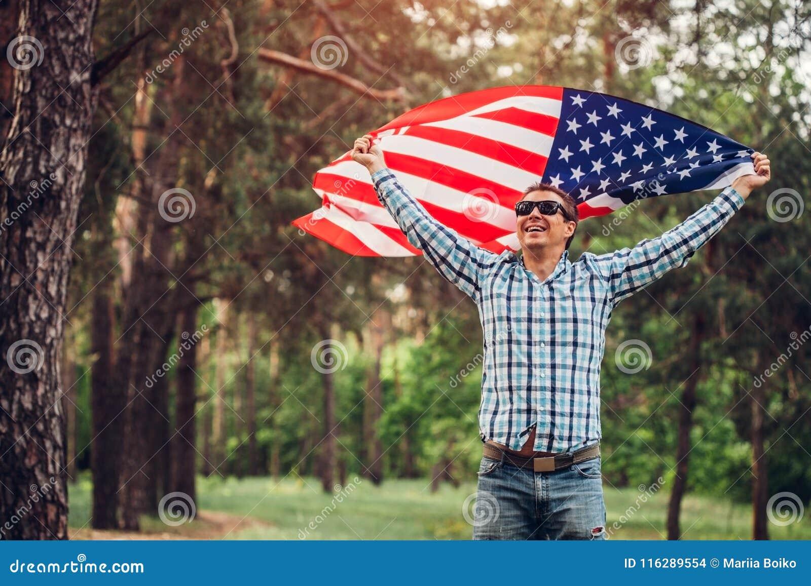Lycklig manspring med USA flaggan Fira självständighetsdagen av Amerika Juli 4th gyckel som har mannen