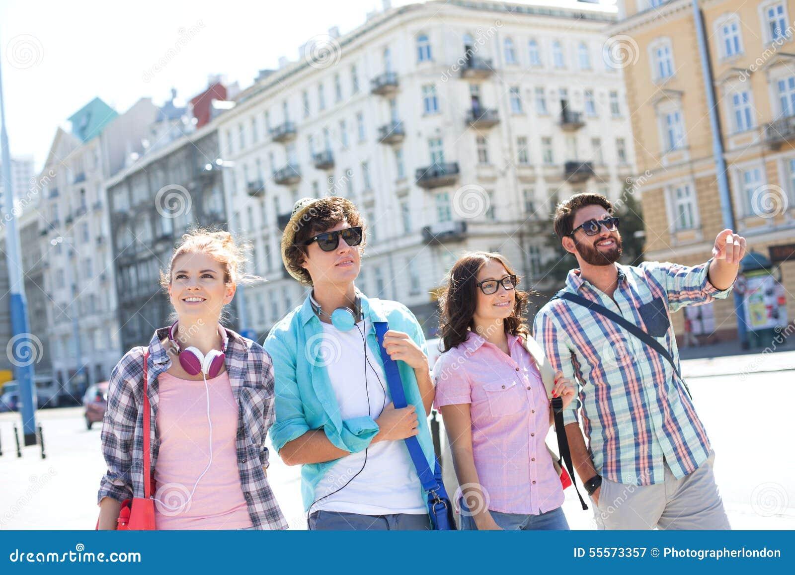 Lycklig manvisning något till manliga och kvinnliga vänner på stadsgatan
