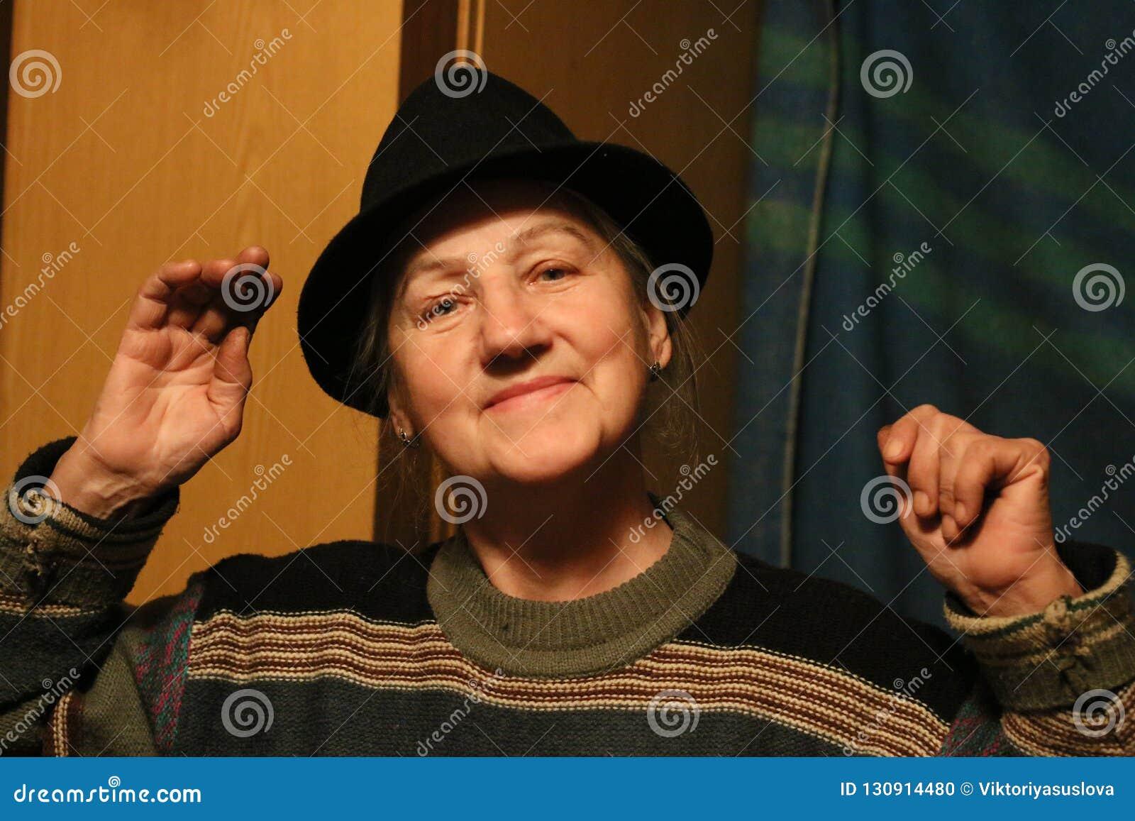 Lycklig mellersta åldrig kvinna i svart hatt