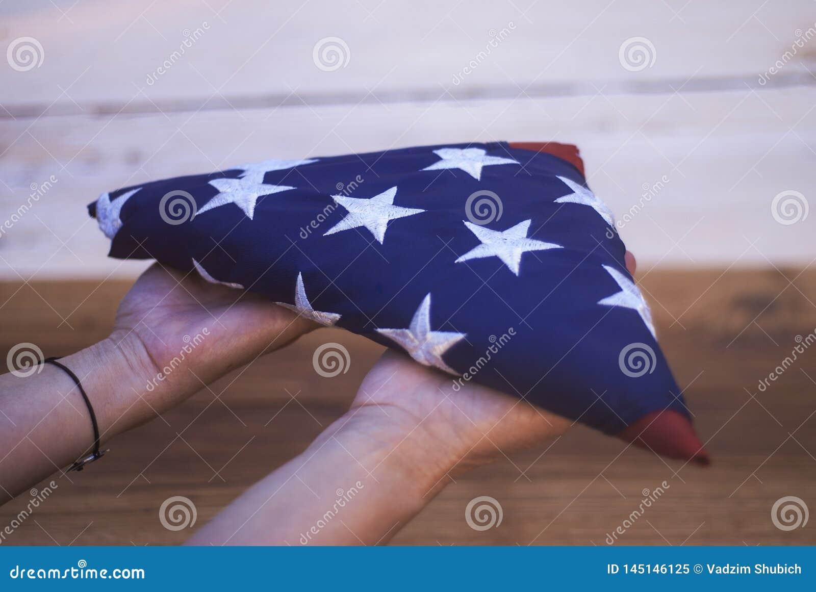 Lycklig minnesm?rke f?r dag Flickan rymmer en vikt amerikanska flaggan i hennes h
