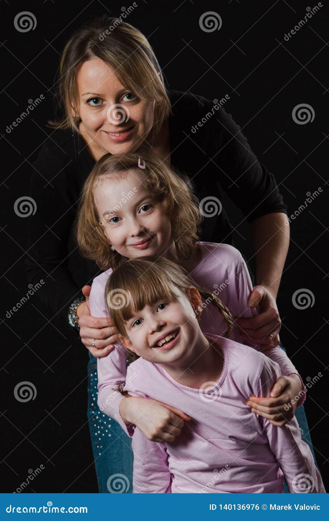 Lycklig moder med två döttrar som lyckligt poserar