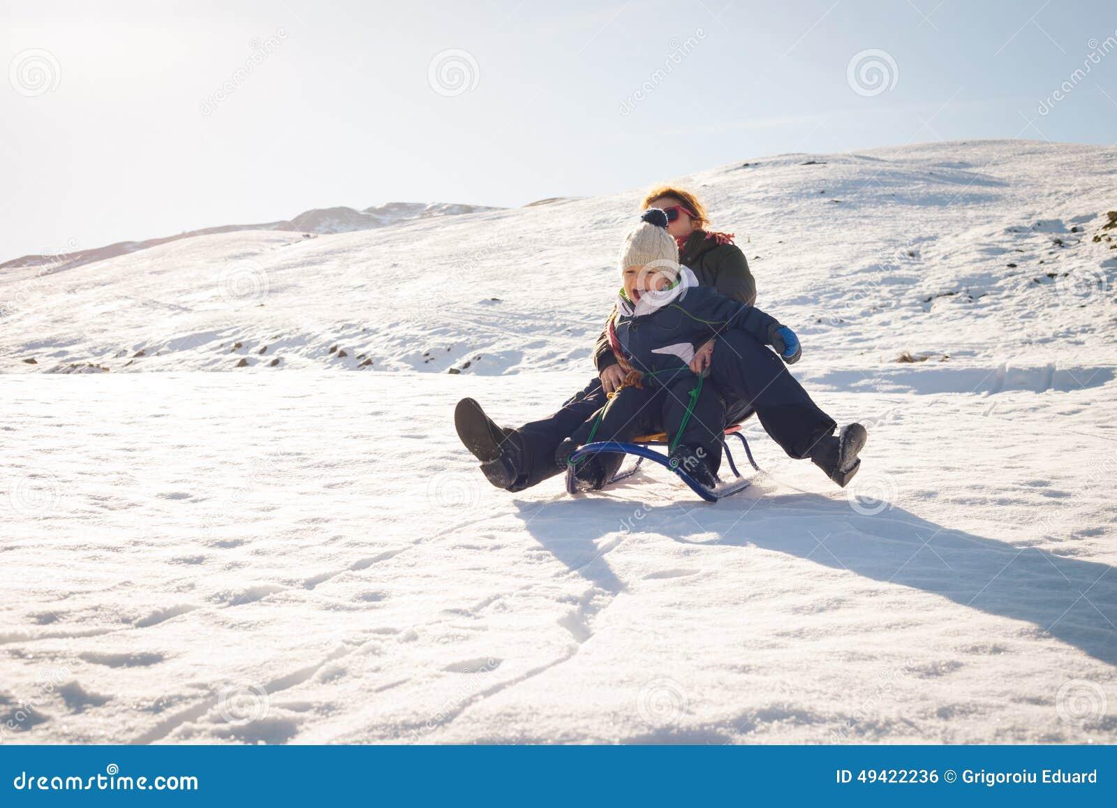 Icke gamla Lycklig Moder Och Barn Som Spelar I Snön Med En Pulka Arkivfoto UI-38