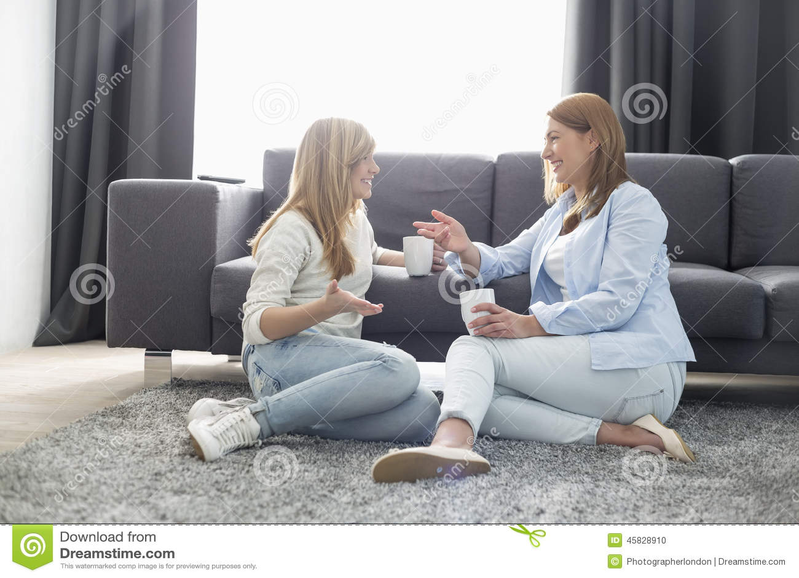 Lycklig moder och dotter som talar, medan ha kaffe i vardagsrum