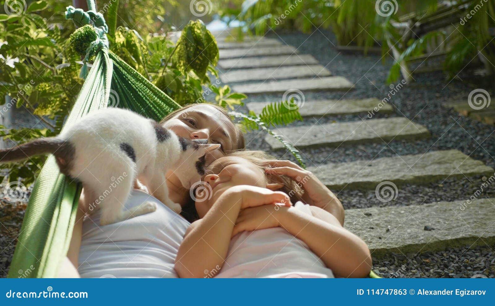 Lycklig moder och dotter som tillsammans kopplar av i en hängmatta på trädgården i sommardag