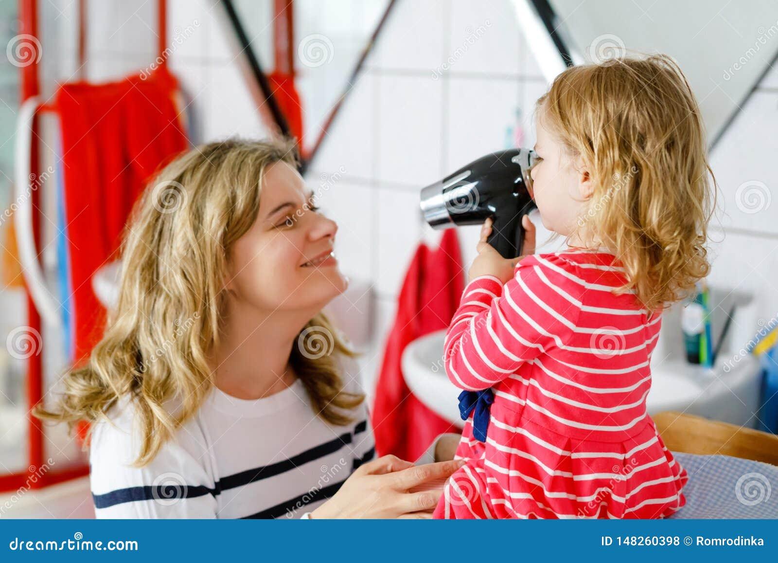Lycklig moder som gör håren av gullig liten litet barnflicka med hårtorken Förtjusande sunt behandla som ett barn barnet med våta