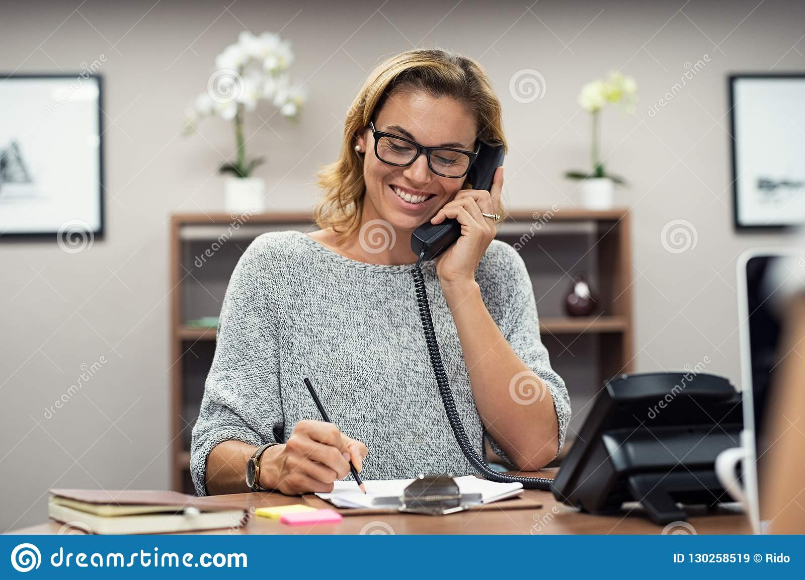 Lycklig mogen kvinna som talar på telefonen