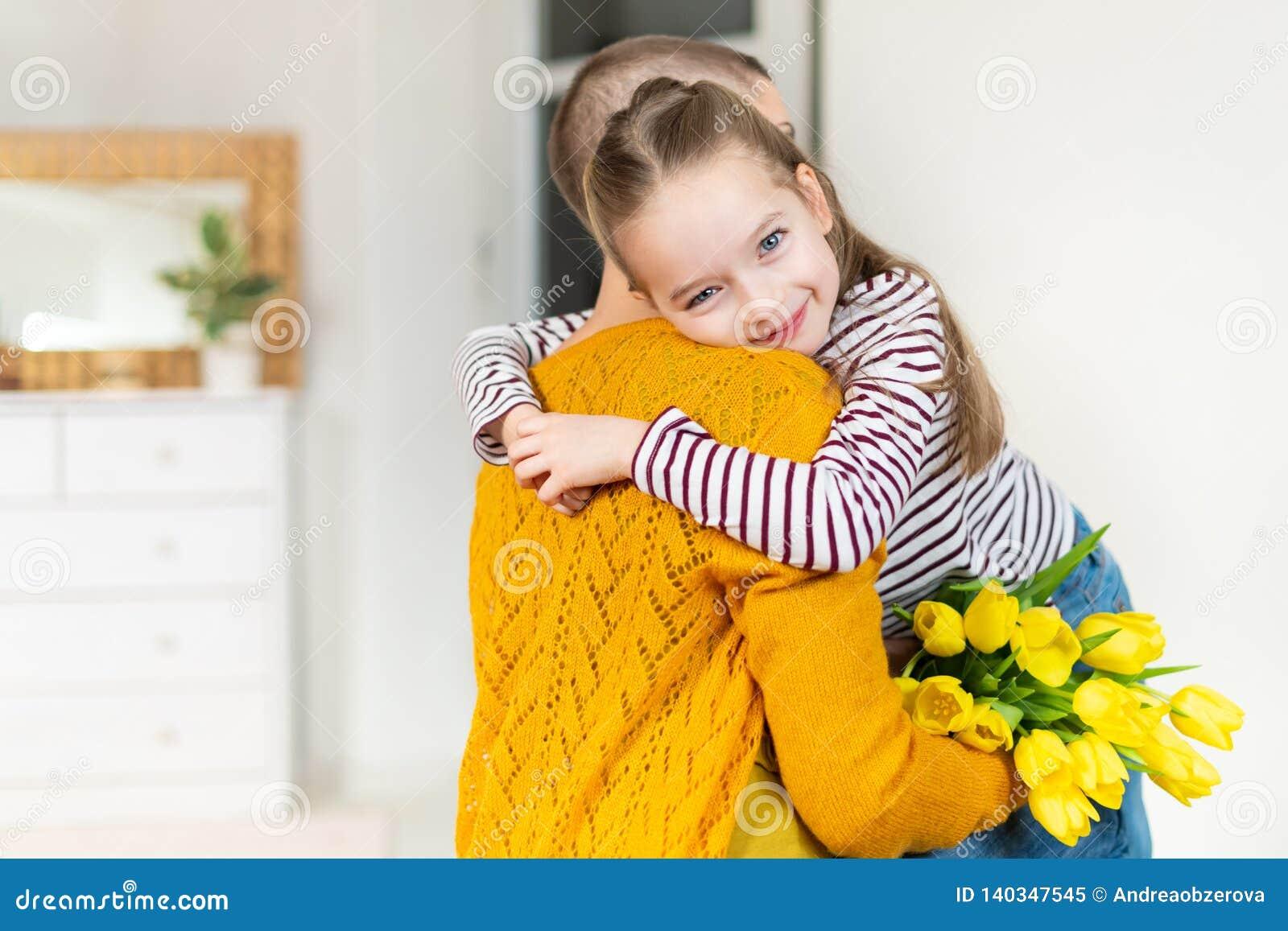 Lycklig mors dag- eller födelsedagbakgrund Förtjusande ung flicka som förvånar hennes mamma, ung cancerpatient, med buketten av t
