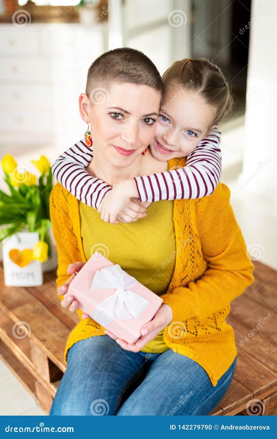 Lycklig mors dag- eller födelsedagbakgrund Förtjusande ung flicka som förvånar hennes mamma, unga cancerpatient, med buketten och