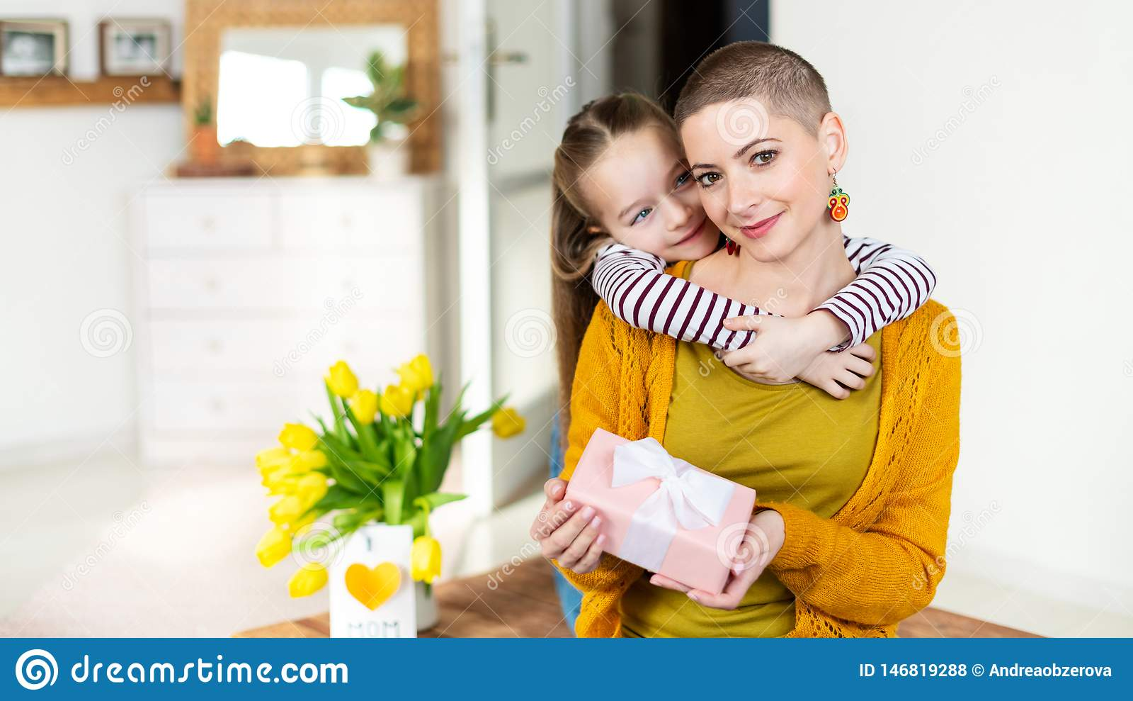 Lycklig mors dag- eller f?delsedagbakgrund F?rtjusande ung flicka som f?rv?nar hennes mamma, unga cancerpatient, med buketten och