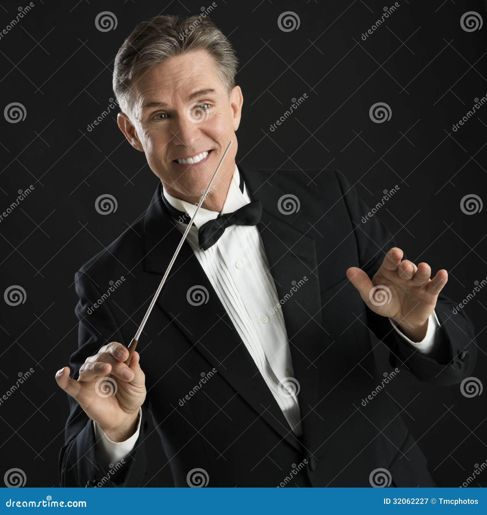 Lycklig musikledare Gesturing While Directing med hans taktpinne