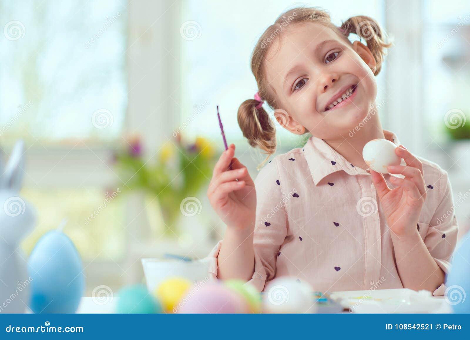 Lycklig nätt barnflicka som har gyckel under målningägg för öst