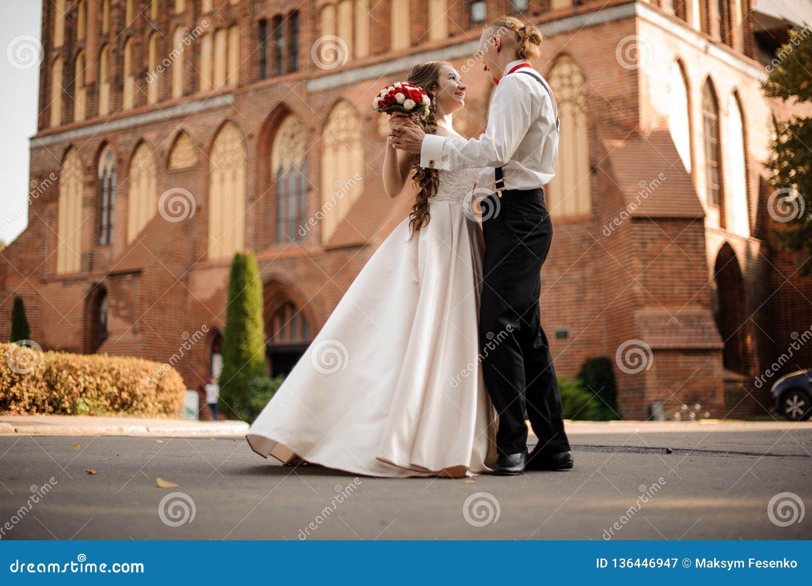 Lycklig och härlig gift pardans i bakgrunden av byggnad för röd tegelsten för tappning med