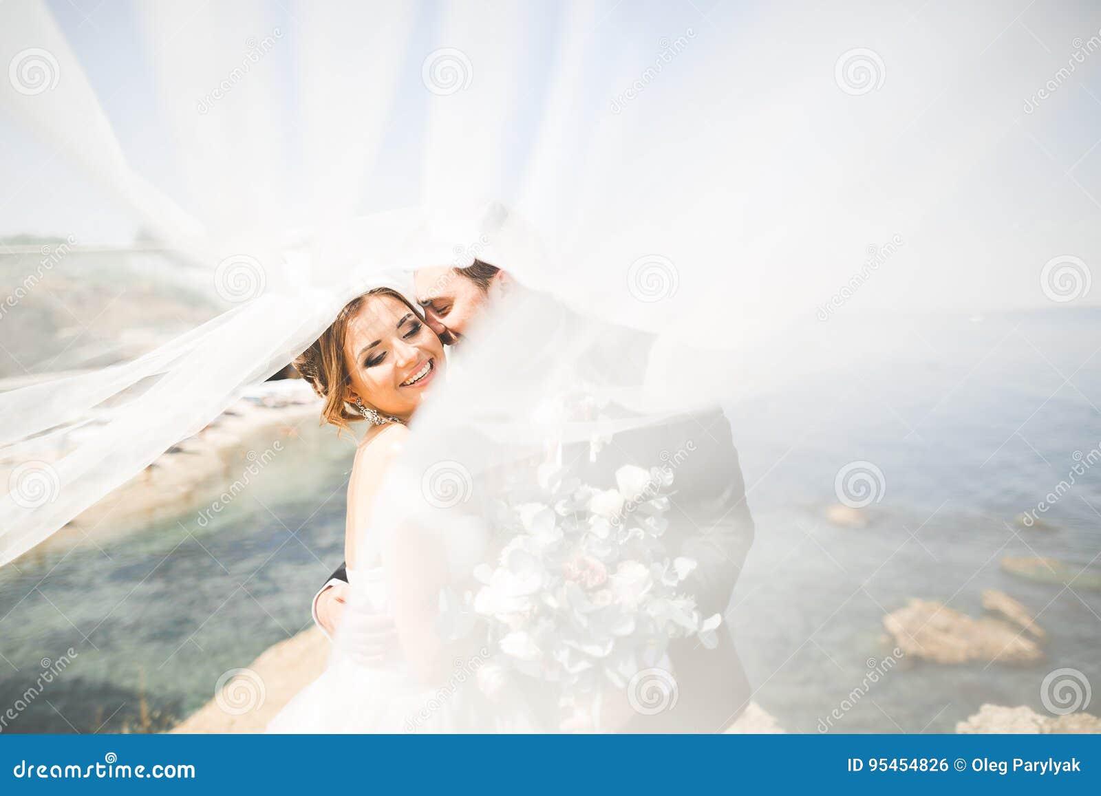 Lycklig och romantisk plats av precis gifta unga brölloppar som poserar på den härliga stranden