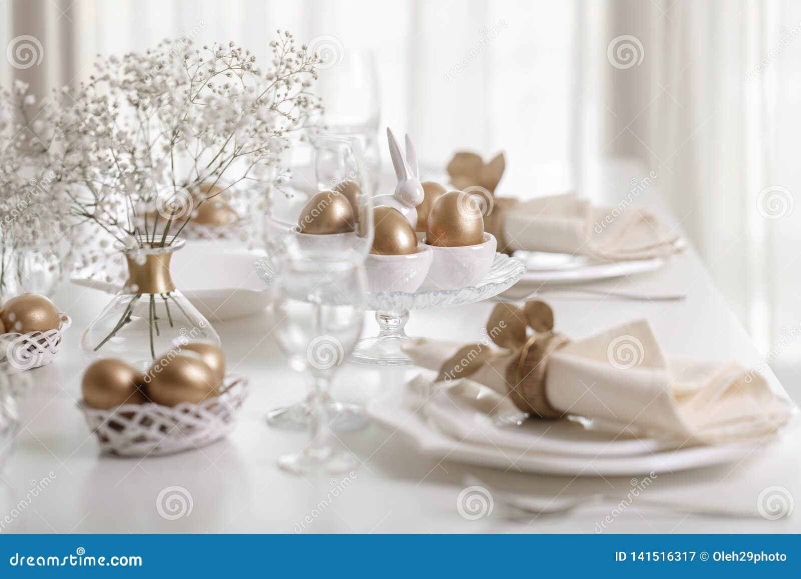 Lycklig påsk! Guld- dekor- och tabellinställning av påsktabellen med vit disk av vit färg