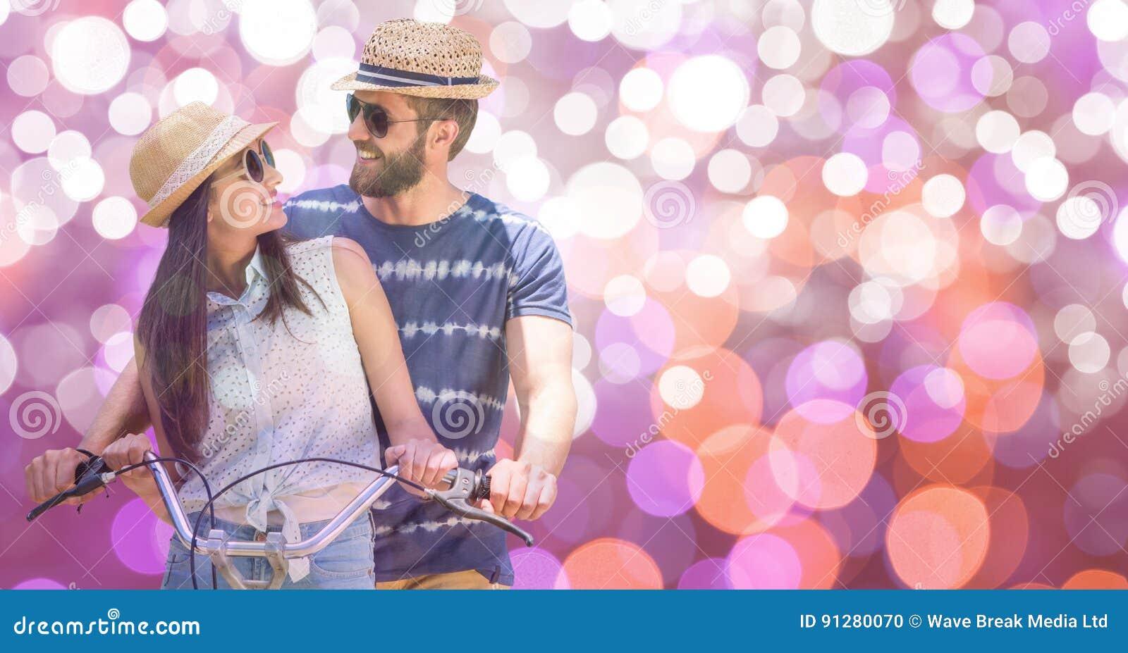 Lycklig parridningcykel under sommarsemester över bokeh