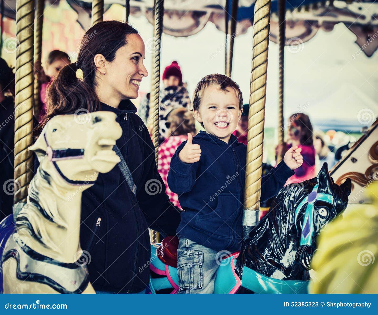 Lycklig pojke och moder på den Retro karusellen -