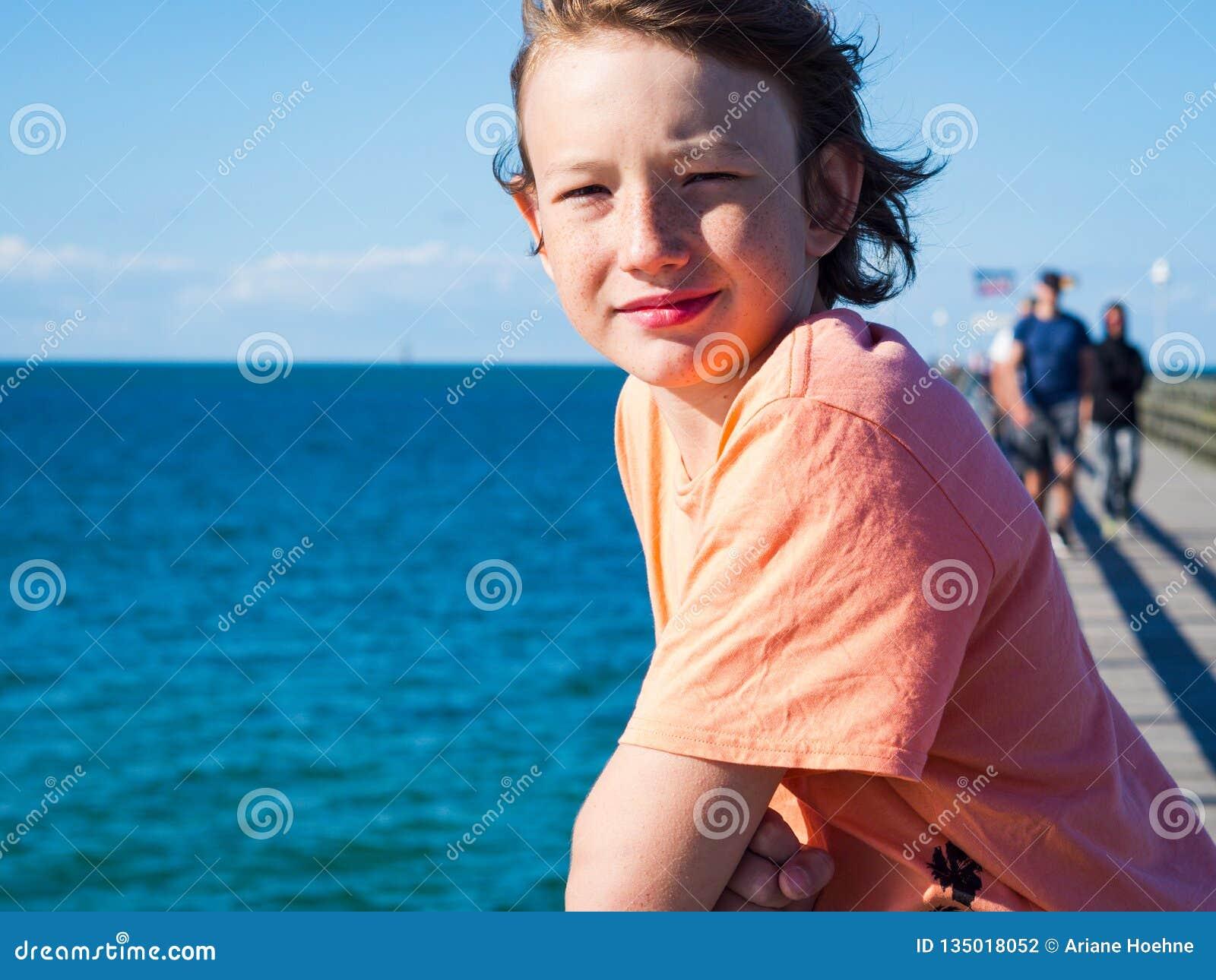 Lycklig pojke på en pir på det baltiska havet