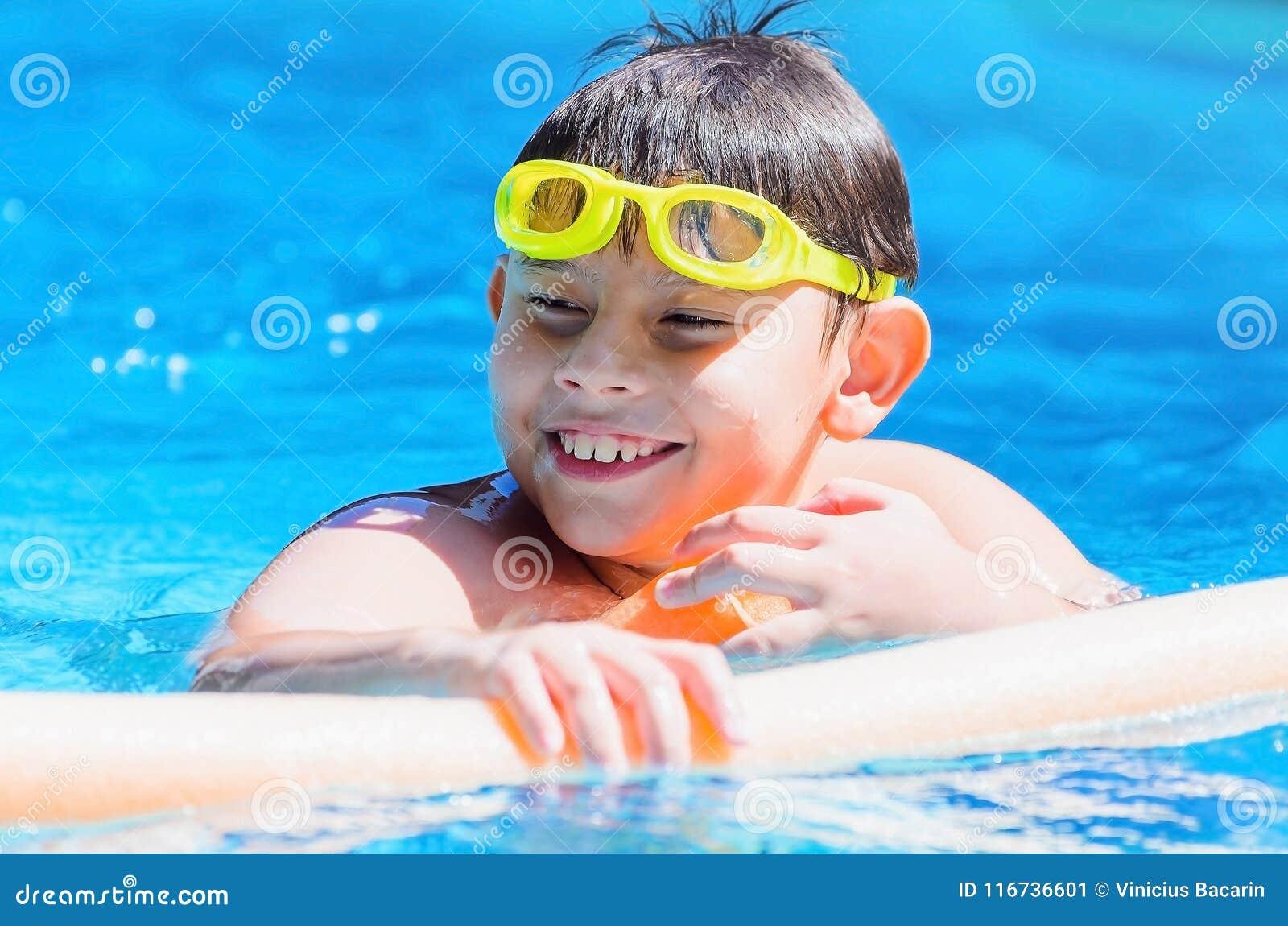 Lycklig pojke på simbassängen, sommartid