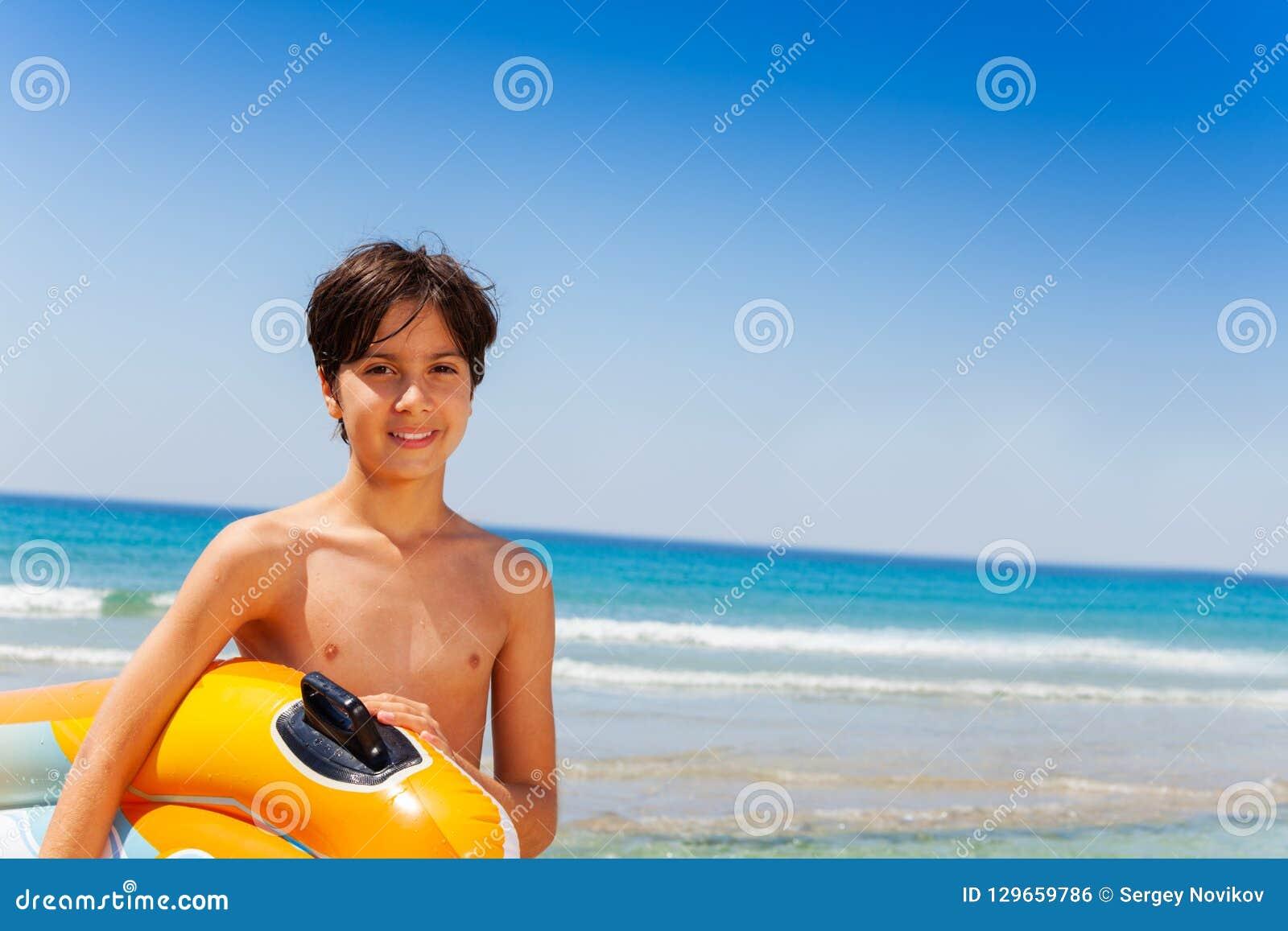 Lycklig pojke som är klar för sommaraktiviteter på sjösidan