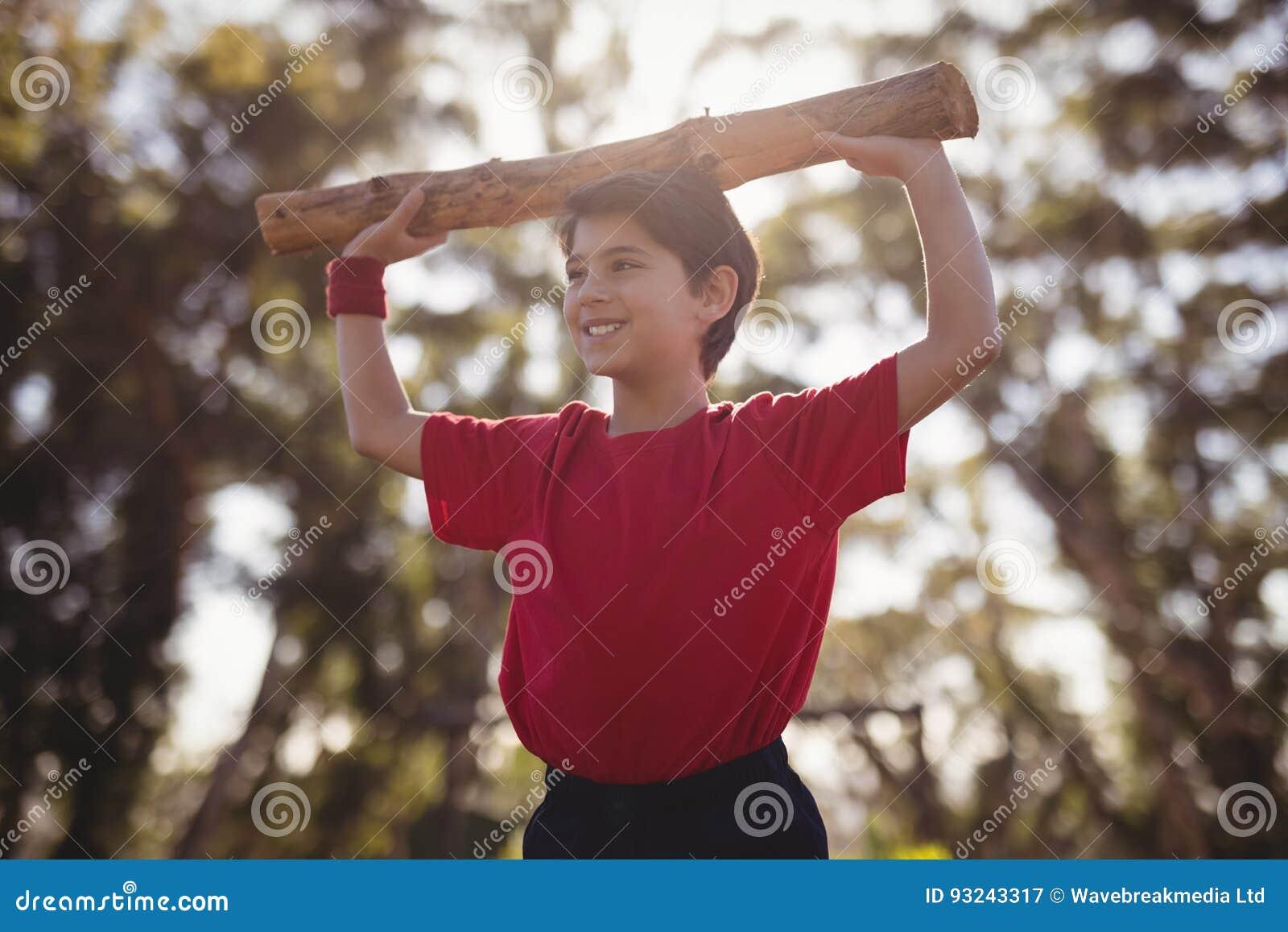 Lycklig pojke som övar med journalen under hinderkurs