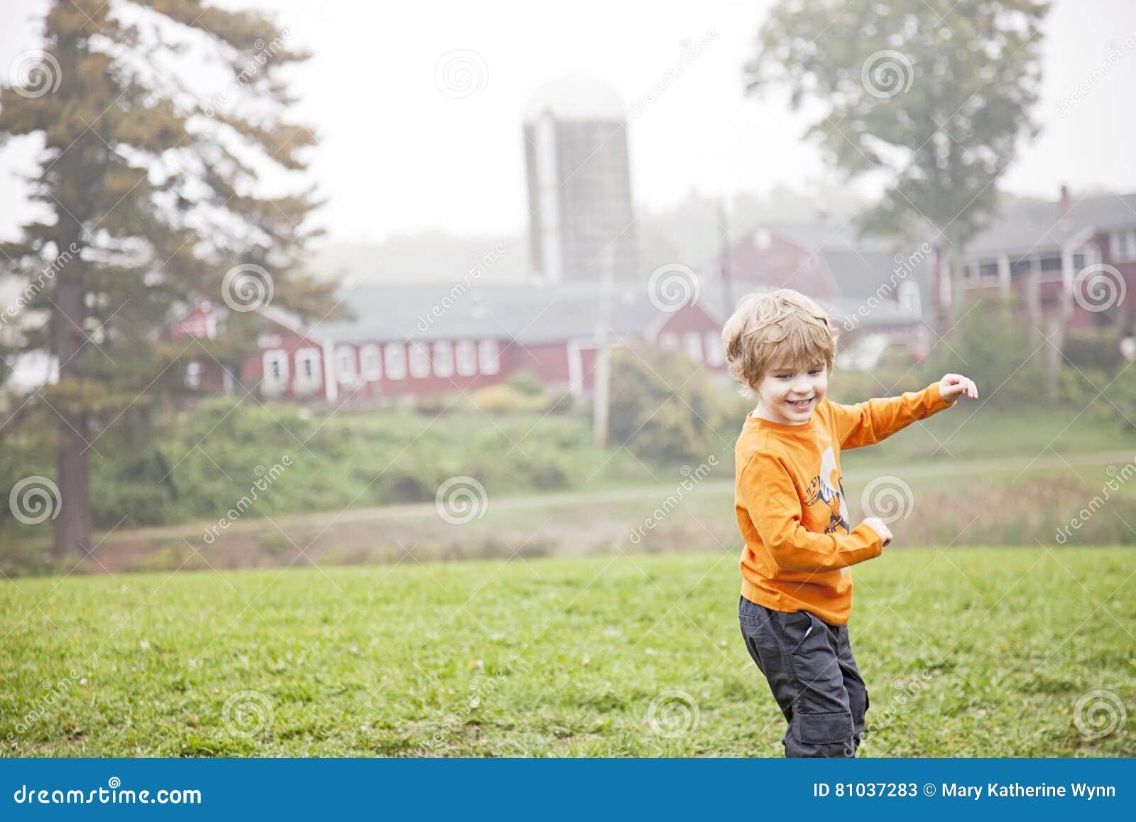 Lycklig pojke som spelar på lantgård