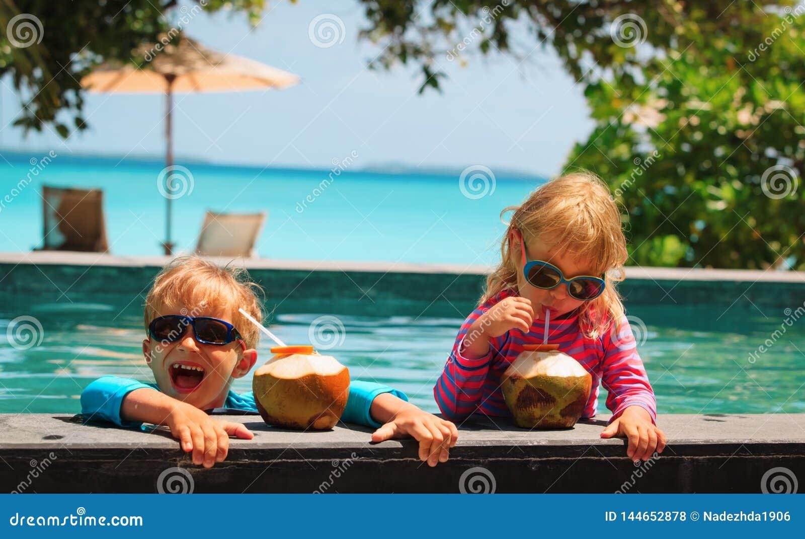 Lycklig pys och flicka som dricker kokosnötcoctailen på strandsemesterort