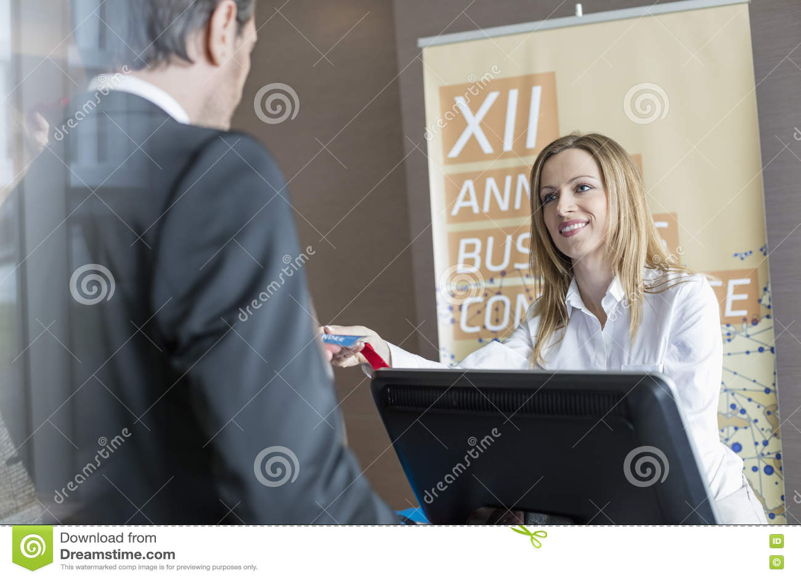Lycklig receptionist som ger identitetskortet till affärsmannen på konventcentret