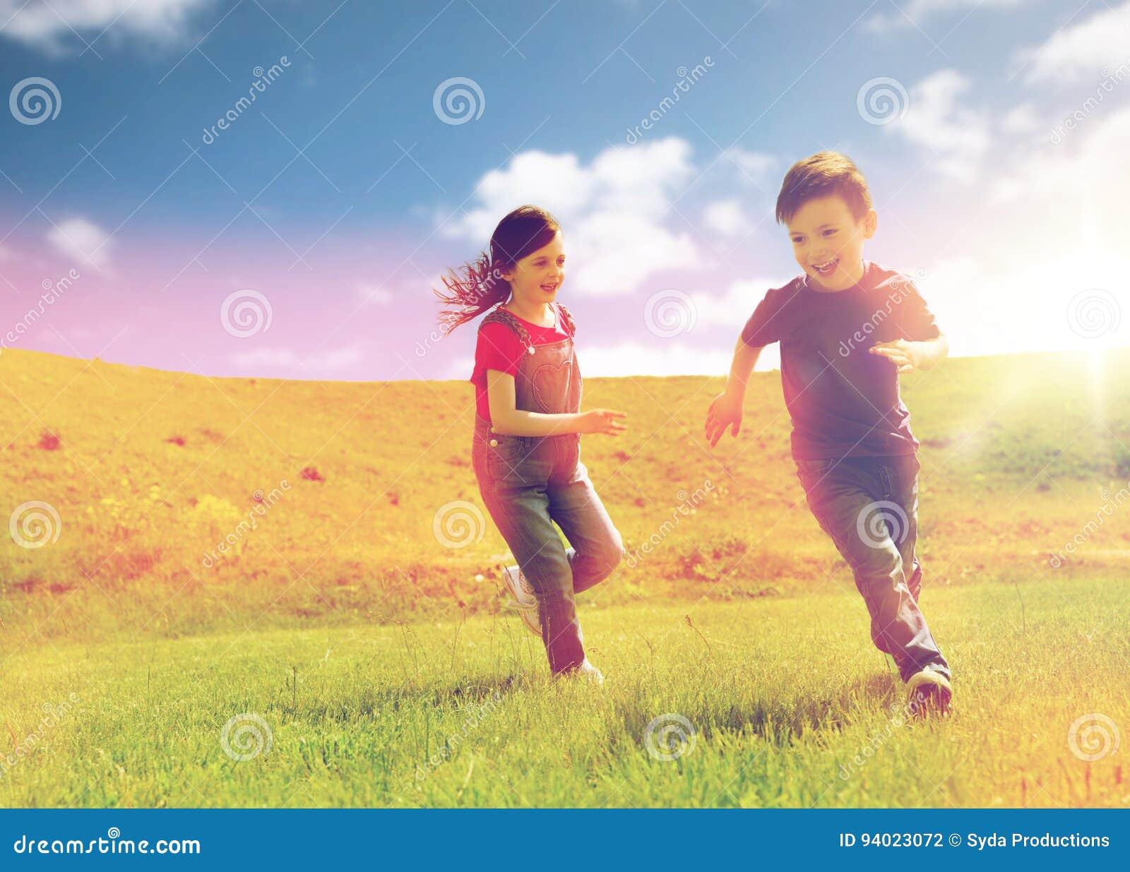 Lycklig rinnande pys och flicka utomhus