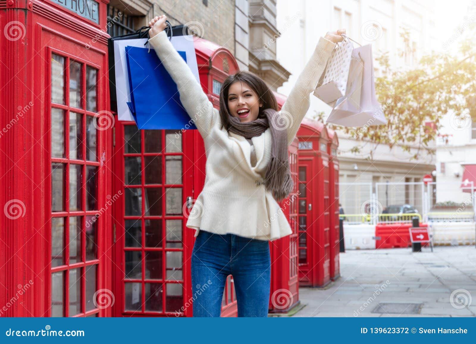 Lycklig shoppa kvinna med shoppingpåsar i hennes hand, London, UK