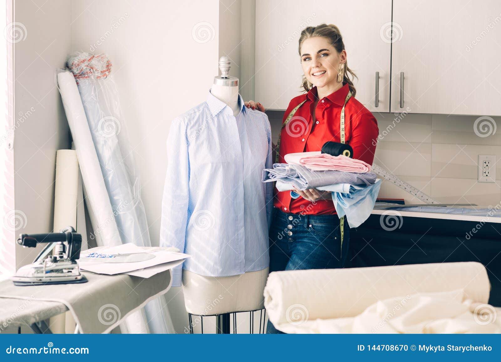 Lycklig skräddarekvinna med nya kläder och skräddarehjälpmedel i hennes designstudioatelier